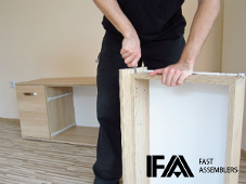 a technician assembling a flat pack chest of drawers